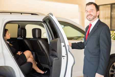 Good looking young Hispanic driver closing the door and driving a very important businesswoman in a car