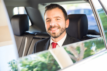 Portrait of a handsome young Hispanic businessman riding in the backseat of a car on a business trip