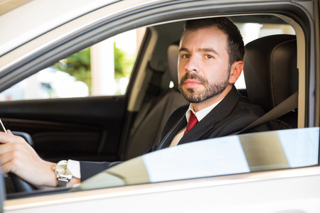 man with beard: Portrait of a handsome young Latin businessman driving a car and making eye contact