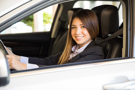 cinturon seguridad: Cute young woman in a suit driving a car with her seatbelt on and smiling Foto de archivo