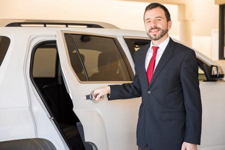 그의 고객 중 하나에 대한 자동차 문을 여는 잘 생긴 전문 드라이버의 초상화