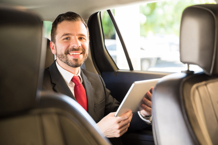 Good looking young man in a suit using a tablet computer while riding a car in a business trip