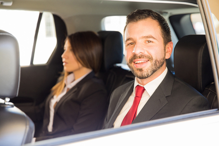 good looking: Portrait of a good looking young Hispanic businessman and a female coworker traveling by car