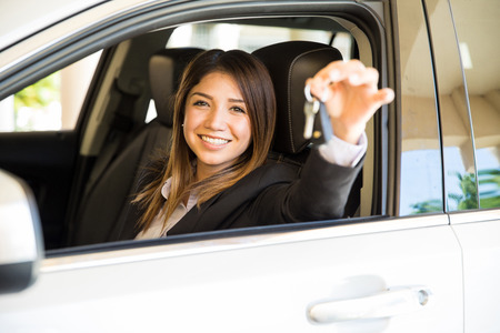 hispanic woman: Portrait of a beautiful young Hispanic woman holding the keys for her new car and ready to drive away