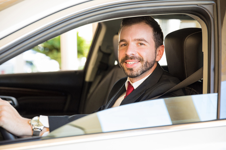 chauffeur: Young male driver in a suit looking out the car window and smiling
