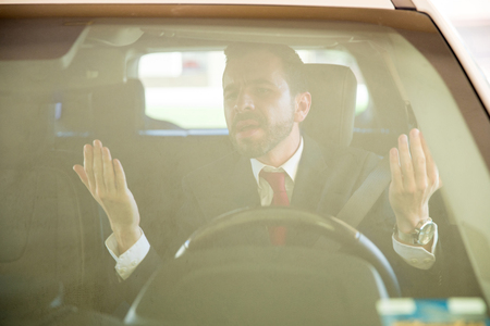 road rage: Angry young man in a suit yelling and cursing to another driver while suffering from road rage