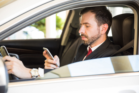 Young man in a suit driving a car and getting distracted by his smartphone Imagens - 66084271