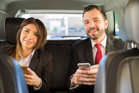 woman business suit: Attractive young Latin businesspeople sitting in the backseat of a car and using their smartphones for work Stock Photo