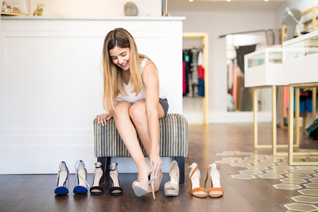 Cute young woman looking to buy some shoes at a fashion store and trying a few of them
