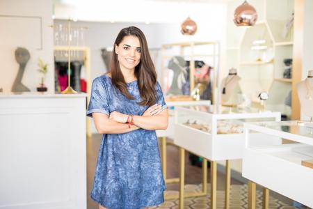 Portret van een aantrekkelijke jonge brunette die zich voor haar juwelenwinkel bevindt met gekruiste wapens