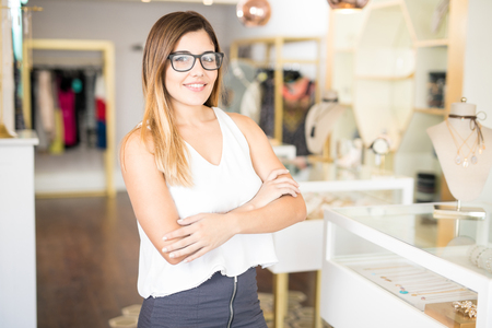 Portrait of a gorgeous young Hispanic business owner standing in front of her jewelry and fashion store