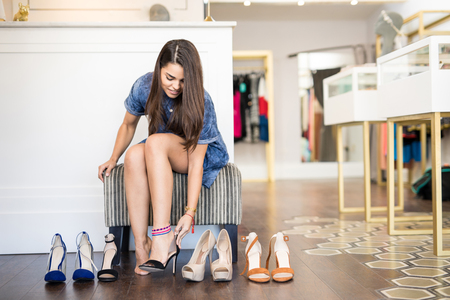 Pretty young brunette trying a few pairs of shoes and deciding what to buy at a fashion store