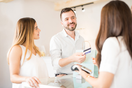 Handsome young Hispanic man buying some jewelry for her girlfriend at a shop Stock Photo