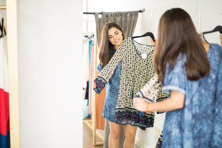 fitting in: Attractive young woman trying on a pretty dress in a fitting room at a fashion store