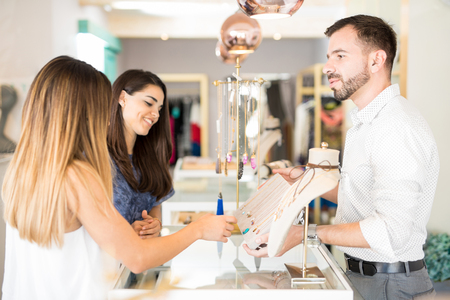 retail store: Profile view of a young handsome man showing some jewelry to a couple of women at a store