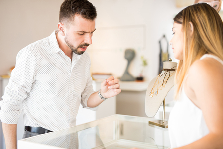 good looking: Good looking young man looking carefully at a diamond ring at a jewelry store Stock Photo