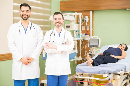 obgyn: Two attractive young doctors standing in a hospital room with a pregnant woman Stock Photo