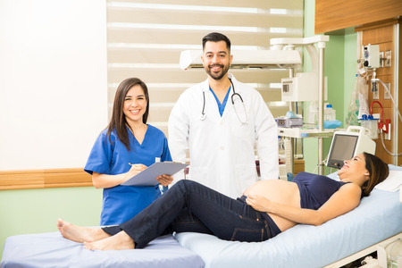Portrait of a handsome Hispanic doctor and a pretty nurse checking on a pregnant woman in a hospital