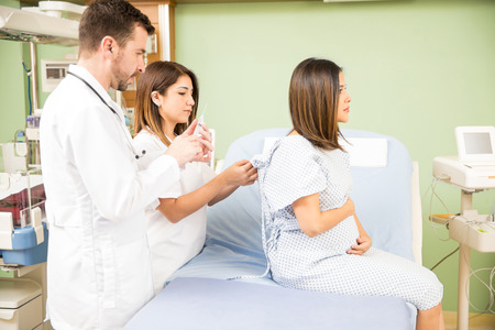 obgyn: Profile view of a young pregnant woman receiving medical attention from a couple of doctors in a hospital
