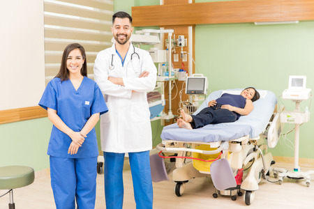 obgyn: Portrait of a handsome Hispanic doctor and beautiful nurse standing in a hospital room with a pregnant patient
