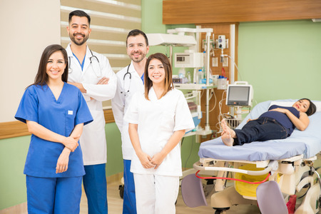 obgyn: Portrait of a group of four doctors and nurses standing in a hospital room with a patient and smiling Stock Photo