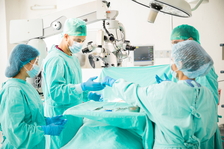 Team of doctors working together during a heart surgery in an operating room at a hospital Stock Photo - 66062193