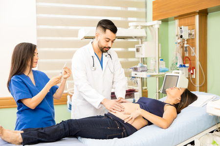 Couple of doctors examining and taking care of a young pregnant woman in pain at a hospital Stock Photo