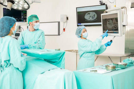 Team of doctors looking at some x-rays during a surgery in an operating room Stock Photo