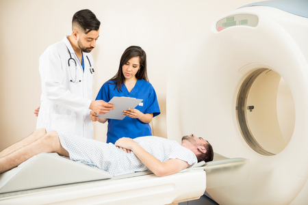Good looking couple of doctors looking at a patients history next to a CT scanner Stock Photo