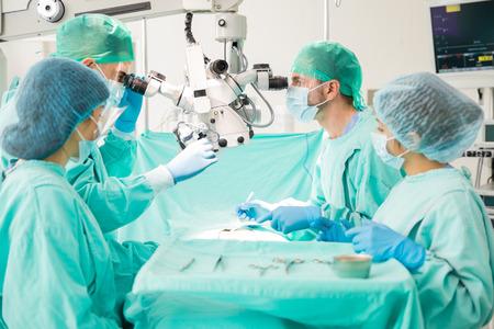 Groep van vier artsen werken aan een patiënt en kijken door een microscoop tijdens de operatie
