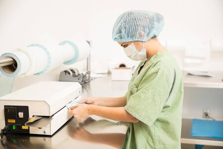 Profile view of a woman in scrubs packing sterile medical instruments in a hospital