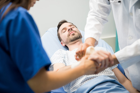 Male patient lying unconsious in a hospital bed while a couple of doctors put on some bandages