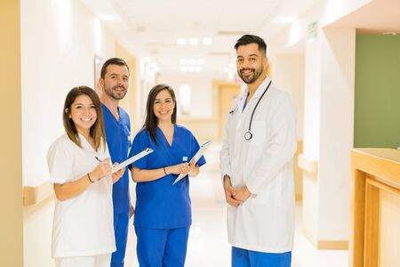 Good looking doctor and a group of medical students standing in a hospital hallway and smiling Фото со стока