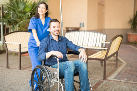 recovering: Handsome male patient being pushing on a wheelchair by a nurse, while going for a stroll in the hospital
