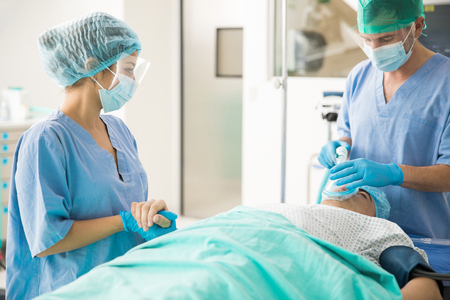 Portrait of a pretty female doctor holding the hand of a patient before he is put under the effect of anesthesia for surgery