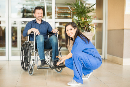 stroll: Beautiful young nurse helping a patient on his wheelchair before going for a stroll in the hospital Stock Photo
