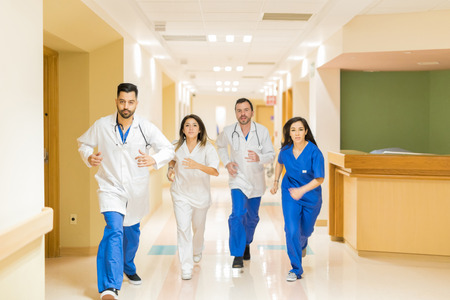 Team of doctors and nurses running down a hospital hallway during an emergency situation