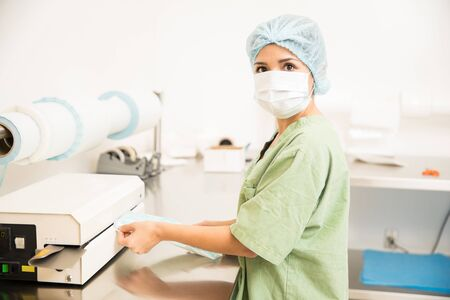 Portrait of a pretty young woman in scrubs packing and sealing sterile medical tools in a hospital and making eye contact