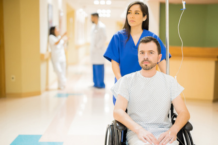 Male patient with a beard taking a stroll in a hospital hallway, being pushed by a nurse