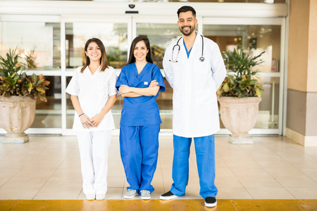 doctors smiling: Full length view of a team of doctors and nurses standing in front of a hospital entrance and smiling