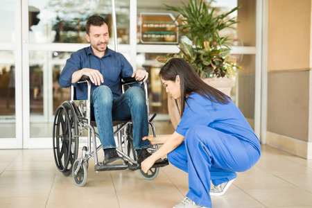 stroll: Pretty nurse helping a patient settle on a wheelchair before going for a stroll outside of a hospital Stock Photo