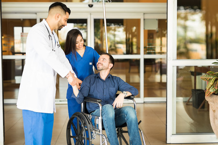 leaving: Happy and recovered patient sitting on a wheelchair and saying goodbye to his doctor while leaving the hospital