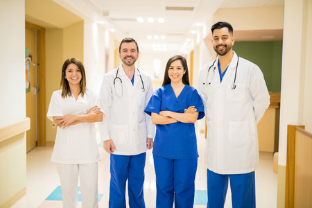Portrait of a team of Hispanic doctors standing in a hospital hallway and smiling