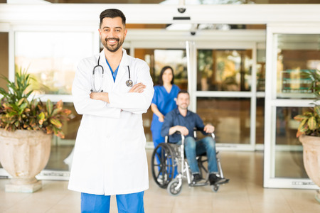 Portrait of an attractive Hispanic doctor standing in the hospital entrance with a patient in a wheelchair in the background