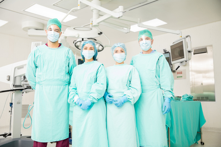 serious doctor: Group of four Hispanic surgeons waiting for a patient in the operating room in a hospital Stock Photo