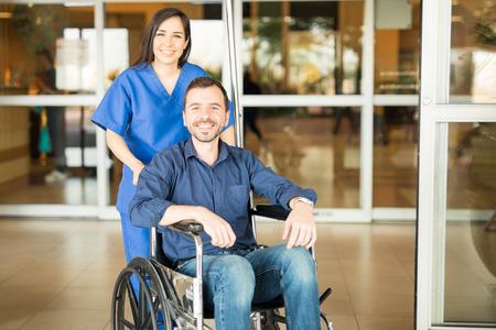 Portret van een jonge Spaanse patiënt die het ziekenhuis in een rolstoel verlaat na een volledig herstel Stockfoto