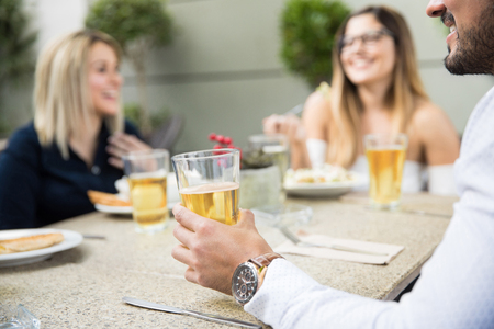 Young man drinking beer with some friends in a restaurant. Closeup of man with beer in the foreground