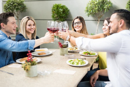 Group of five attractive young friends making a toast with wine while eating together in a restaurant