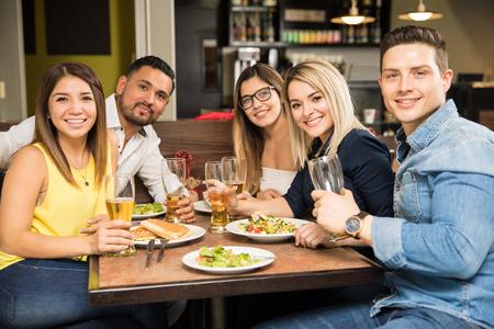 Portret van een groep van vijf knappe Spaanse vrienden die en in een restaurant eten drinken Stockfoto