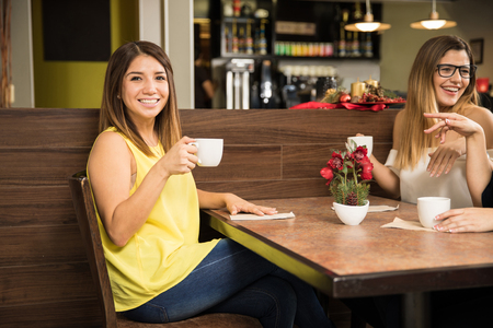 women coffee: Attractive young brunette enjoying a cup of coffee with her female friends at a restaurant Stock Photo